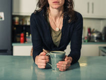 Young woman drinking coffee in kitchen Stock Images