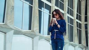 Young woman drinking coffee on a modern building background stock video footage