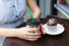 Young woman drinking coffee with muffin in outdoors cafe. Close up Royalty Free Stock Images