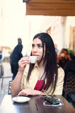 Young woman drinking coffee at outdoor city table Stock Photo
