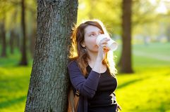 Young woman drinking coffee outdoors. Dreamy young woman drinking coffee or tea outdoors Stock Images