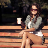 Young woman drinking coffee from paper cup. Sitting on bench Royalty Free Stock Photography