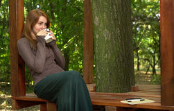 Young woman drinking coffee in the park Royalty Free Stock Photography