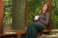 Young woman drinking coffee in the park Stock Photography