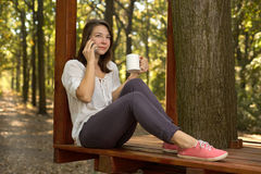 Young woman drinking coffee in the park Royalty Free Stock Photos