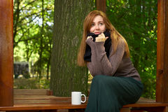 Young woman drinking coffee in the park Stock Image