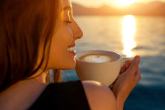 Young woman drinking coffee on the pier at sunrise Royalty Free Stock Photography