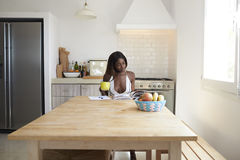 Young woman drinking coffee and reading in her kitchen Stock Photography