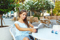 Young woman drinking coffee and reading the newspaper in cafe Royalty Free Stock Image