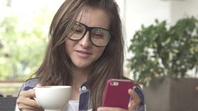 Young woman drinking coffee and sending messages with her mobile phone. In cafe stock footage