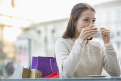 Young woman drinking coffee at sidewalk cafe Royalty Free Stock Images