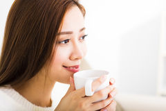 Young woman drinking coffee and sitting on sofa Stock Photo