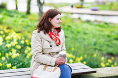 Young woman drinking coffee in spring park. Royalty Free Stock Photo