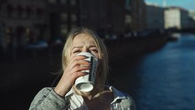 Young Woman Drinking Coffee In The Street. Portrait of young woman drinking coffee in the street and sees something in the sky stock video footage