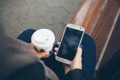 Young woman is drinking coffee on the street while sitting on bench on cold winter day. Close-up of hands with white take away cup of hot coffee and mobile Royalty Free Stock Photos
