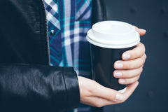 Young woman is drinking coffee on the street while walking in the city center. Close-up of hands with beautiful natural manicure holding take away cup of hot Stock Photos