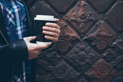 Young woman is drinking coffee on the street while walking in the city center. Close-up of hands holding take away cup of hot coffee. Copy-space blank for your Royalty Free Stock Photo