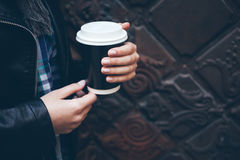 Young woman is drinking coffee on the street while walking in the city center. Close-up of hands holding take away cup of hot coffee. Copy-space blank for your Stock Photo