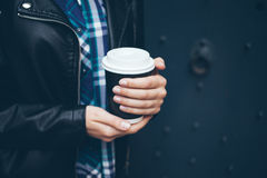 Young woman is drinking coffee on the street while walking in the city center. Close-up of hands with take away cup of hot coffee. Copy-space blank for your Royalty Free Stock Photography