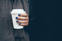 Young woman is drinking coffee on the street while walking on cold winter day. Close-up of hands with white take away cup of hot coffee. Copy-space blank for Stock Photos