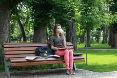 Young Woman Drinking Coffee. Young student woman drinking coffee while studying outdoor in a park Stock Photos