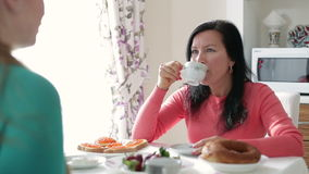 Young woman drinking coffee and talking. A conversation between two young woman at breakfast. Young women talking over coffee. Breakfast two young woman stock footage