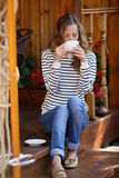 Young woman drinking coffee or tea sitting on the porch Royalty Free Stock Image