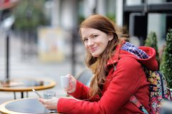 Young woman drinking coffee and using her smart phone Royalty Free Stock Photography
