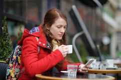 Young woman drinking coffee and using her smart phone Royalty Free Stock Photo