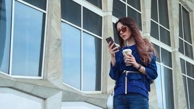 Young woman drinking coffee and using smartphone in a business district. Urban modern city concept stock video