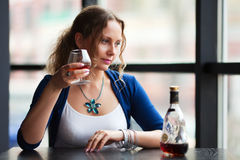 Young fashion woman drinking cognac at restaurant Stock Photo