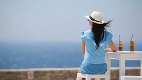 Young woman drinking cold coffee enjoying sea view. Beautiful woman relax during exotic vacation on the beach enjoying