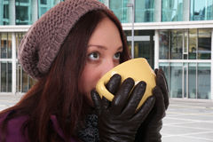 Young woman drinking cup of tea in winter outdoors in town Royalty Free Stock Photos