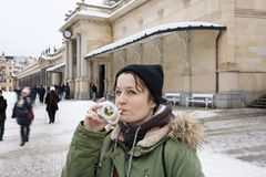Young woman drinking from cup with therapeutic mineral water at a natural hot spring in Karlovy Vary during winter time. Czech Republic royalty free stock images