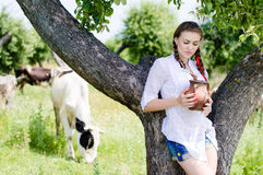 Young woman drinking fresh milk near cows in countryside Stock Photos