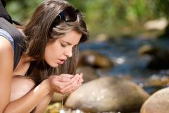 Young woman drinking fresh water from stream in nature Royalty Free Stock Photography