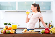 Young woman drinking a glass of orange Juice in the kitchen.III Stock Photography