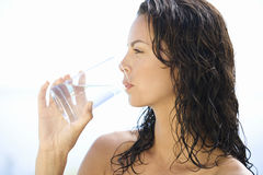 A young woman drinking a glass of water Stock Photography