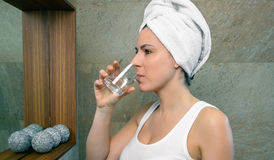 Young woman drinking glass of water in bath Royalty Free Stock Photos