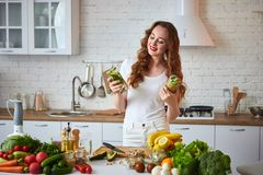 Young woman drinking green smoothie and fresh water with cucumber, lemon, leaves of mint on the kitchen table with fruits and. Vegetables . Healthy eating stock image