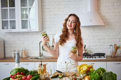 Young woman drinking green smoothie and fresh water with cucumber, lemon, leaves of mint on the kitchen table with fruits and. Vegetables. Healthy eating stock images