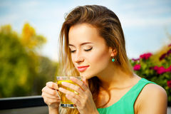Young Woman Drinking Green Tea Outdoors. Summer Background. Shallow Depth of Field Royalty Free Stock Image