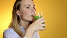 Young woman drinking green vegetable smoothie stock video