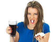 Young Woman Drinking High Sugar Fizzy Drink. A DSLR royalty free image of an attractive young woman with dark blonde hair, showing how much sugar is in a glass royalty free stock photography