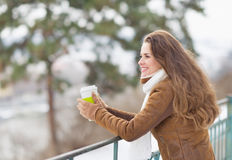 Young woman drinking hot beverage in winter park. Young woman drinking hot beverage and looking into distance in winter park Royalty Free Stock Photo