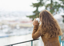 Young woman drinking hot beverage in winter park. Young woman drinking hot beverage and looking into distance in winter outdoors. rear view Stock Image