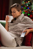 Young woman drinking hot chocolate and watching TV Stock Photo