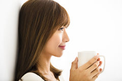 Young Woman drinking hot latte coffee. In living room Royalty Free Stock Image