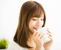 Young Woman drinking hot latte coffee. In living room Royalty Free Stock Images