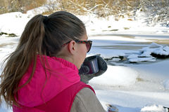 Young woman drinking hot tea on winter forest. And watching frozen river Stock Photo